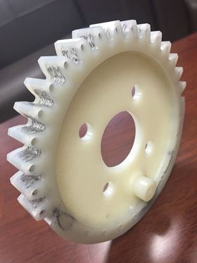 The plastic gear wheel reinforced with carbon fiber fabric.