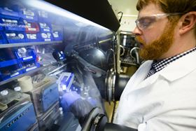 Nathan Taylor, a post-doctoral fellow in mechanical engineering at the University of Michigan, inspects a piece of lithium metal. Photo: Evan Dougherty/Michigan Engineering Communications & Marketing.