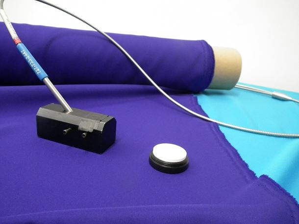 The violet prototype and a typical blue polyester, with a reflectance probe and a white reflectance standard, part of the kit used for measuring color properties